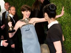 Anne Hathaway, carrying her Oscar for best supporting actress, happily greets comedian Sarah Silverman as they arrive for the 'Vanity Fair' party. Adrian Sanchez-Gonzalez, AFP/Getty Images