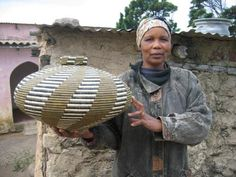 Africa | Beauty Ngxongo, a master basket weaver from South Africa, holding one of her baskets