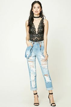 A pair of jeans featuring a distressed design, removable adjustable suspender straps, a five-pocket construction, and a zip fly.