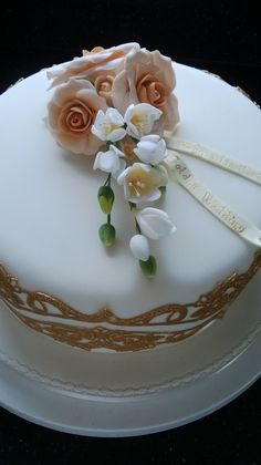 Golden Wedding anniversary cake, using gold lace, sugar roses and freesias.