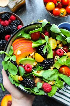 Bright and tangy fruit and nut summer salad with blackberries, raspberries, cherry tomatoes, avocado and toasted hazelnuts - all…