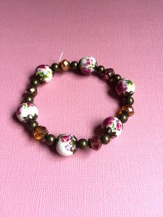 Handmade bracelet for that vintage style loving gal in your life! A perfect gift for Mothers Day, a birthday, an anniversary, the holidays, or to show you care!  This bracelet is made with stretchy elastic string, so it fits most sizes of wrists easily with no difficult latches. In this particular bracelet, mauve glass beads compliment purple floral porcelain pearls, tied together with antique bronze findings. Larger quantities limited for this product but do not hesitate to contact me to…