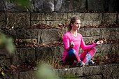 Young woman sitting cross legged on stone steps meditating looking away - Stock Photo