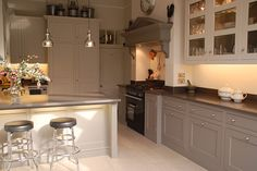 photo of classic contemporary modern vintage neutral colours traditional grey glass cupboards wood surface wooden hello of mayfair kitchen with white kitchen cabinets fireplace lights and cooker range cooker glass fronted cabinet Taupe Kitchen, White Kitchen Cabinets, Wooden Kitchen, Cupboards, Bespoke Kitchens, Grey Kitchens, Home Kitchens, Fitted Kitchens, Open Plan Kitchen