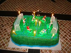 Soccer field cake out of buttercream icing with soccer decorations.