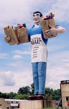 Related Members of the Muffler Man Family - Big John - A grinning, towering colossus of a grocery store clerk, beefy arms bowed outward to accommodate giant bags of groceries. Manufactured by a company in Missouri and primarily deployed in Illinois. So none of the original M-Men molds, and made by a different company. But still, we consider him part of the extended family.