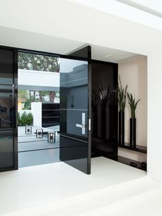 Glossy doors are uncommon as well. White stripes offer a response to the black strips along the exterior walkway. Inside, glossy walls and floors continue the highly polished theme.