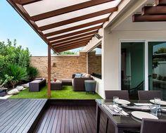 aménagement petit jardin dans l'arrière-cour avec pergola, mobilier en rotin et gazon