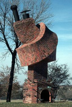 "The sculpture titled ""Performance Piece"" is by renowned sculptor Dennis Oppenheim. The sculpture is made from steel, pigments, bugles, firebrick and fiberglass. It features a fireplace and chimney with the chimney twisted in a knot. Around the fireplace are several bugles."