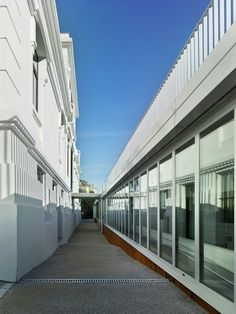 Díaz & Díaz Arquitectos. A Coruña, Madrid. School architecture. Rehabilitation and expansion of a modernist building for classrooms. Facade. Old. New. Glass. White. Color. Walkway. Heritage