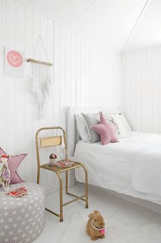 white + blush pink girl's room | vintage inspired chair | layers of pillows | painted white planked walls