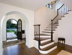I love the round top doors and curved staircase. (Still, it needs a runner.)