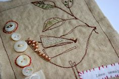 1. Make a sketch. 2. Adhere interfacing to back of linen piece. Transfer sketch to interfacing with carbon paper. Then start stitching by hand or machine or both, using transferred lines as guides. 3. Add embellishments like buttons, beads, etc....