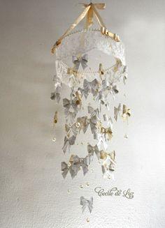 Exclusividade Cecile de Luz Móbile para quarto de bebê super elaborado para uma decoração suave e chique ao mesmo tempo.   - 40 laços origami em papel de scrapbook  rendado em 2 tons, bege e dourado. - Pérolas em 4 tamanhos - Renda chamousse - Laços de cetim  estilo chanel - Aro de 27 cm por 90 cm comprimento total R$ 288,00