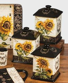 French Sunflowers Canister Set, by Certified International. Features artwork by Tre Sorelle Studios of bees, french writing, and sunflowers in a palette of black, cream, and golden yellows. This is for the Canisters, which come as a set of 3. 56, 60, and 96 ounce capacity, rubber gasket seals.