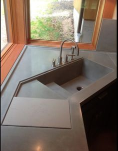 Integral Concrete Kitchen Sink  Visit Store »  This kitchen sink was a new custom design created by VC Studio Inc. It includes an integral drainboard with rails for a sliding cutting board.