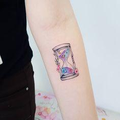 Tatuagem feita pela tatuadora Jacke Michaelsen de Curitiba.  Ampulheta colorida no antebraço.