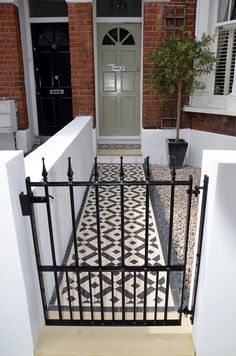 Plastered rendered front garden wall painted white metal wrought iron rail and gate victorian mosaic tile path in black and white scottish pebbles York stone balham london Victorian Front Garden, Victorian Terrace, Victorian Homes, Up House, House Front, Terrace House Exterior, Edwardian Haus, Front Path, Iron Front Door