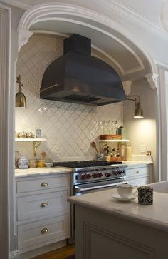 Beautiful brownstone kitchen with creamy white cabinets paired with marble countertops and Mission Stone and Tile Beveled Arabesque Tile in Glossy White backsplash.