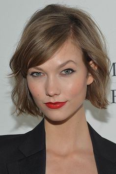 Karlie Kloss Best Beauty Moments | If you've ever wanted to recreate everyone's favorite timeless trend (Parisian chic), here's how: a clean application of red lipstick and winged liner paired with mussed-but-not-messy hair and a menswear-inspired ensemble. (Supermodel legs optional.)