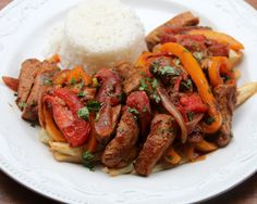 Pork lomo saltado or Peruvian inspired pork stir fry recipe made with pork tenderloin strips, red onions, garlic, peppers, tomatoes, cumin, vinegar, soy sauce, cilantro and green onions. Served with french fries and rice.