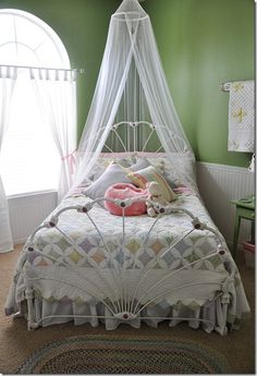 beautiful girls room - cool curtains over bed! antique quilt + sheer hanging over bed + braided rug in middle of room