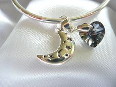 This is a delicate bangle bracelet made of sterling silver. Hung from it is a beautiful sterling silver crescent moon charm that is decorated with stars and moons, partnered with a single beautifully cut blackish grey heart shaped Swarovski Crystal.  Both the crystal and the sterling silver charm dangle delicately from this stunning bangle bracelet.