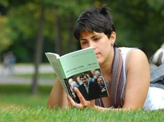 girl reading book outside college