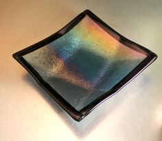 Clear irid, over Steel Blue with black border slumped in folded square bowl.
