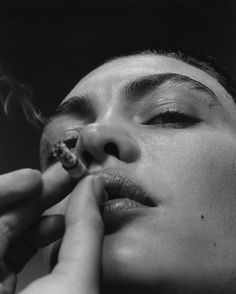 black and white, low angle close up to focus on the cigarette and mood on her face