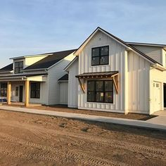 White farmhouse with large front covered porch, black roofing, wood beams and black Anderson windows. White Farmhouse Exterior, Farmhouse Windows, Modern Farmhouse Plans, Farmhouse Style, Industrial Farmhouse, Modern Exterior, Farmhouse Decor, Morton Building Homes, Metal Building Homes