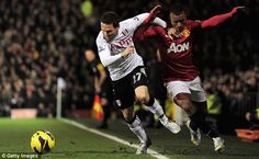 Fulham's Sascha Riether forces Manchester United's Nani off the pitch