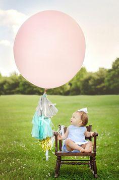 DIY giant balloon tassel fringe!  First Birthday photo shoot outdoors!  www.pineapplesandpeonies.com