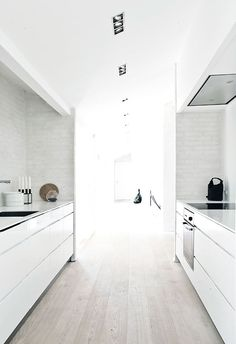 Kitchen: pale grey timber floorboards, gloss white handleless cabinets, undermount rangehood, exposed brick walls rendered and painted white