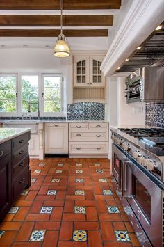 Spanish Revival house kitchen with fabulous terracotta and California deco tiles floor, white traditional perimeter cabinets, dark wood center island, marble counters, blue and white pattern wall tiles, BlueStar range, white stucco range hood.