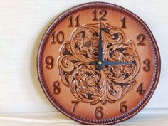 This one of a kind 8 inch Leather clock. Is hand tooled and stitched. Clock motor and hands are made by Takane (made in USA) with an on / off switch. It uses a single AA battery. ( Special note  There is a blemish on the top back side by the wall hanger.)