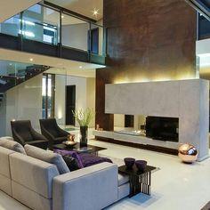 Sala de estar com sofás begecreme e poltronas pretas, pé direito duplo e parede marrom, guarda corpo em vidro e mesa de centro.