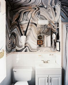Marbleized paper from an art supply shop covers the walls and ceiling in a bathroom. From Lonny Mag.