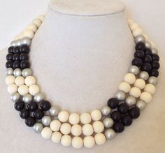 This versatile three-strand black and white colorblock necklace is simple in design, but makes a statement. Silver beads accent the black and white