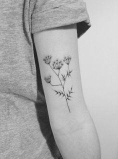 Delicate flower tattoo on the left bicep. Tattoo artist: Lara M....
