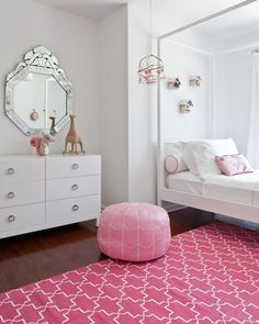 The bright pink rug immediately catches your eyes in this bedroom. The white bedspread and dresser balance out this bold rug.