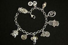 A collection of silver plated Hindu and Buddhist themed charms have been dispersed around a shimmering silver plated bracelet chain in this handmade charm bracelet. This handmade bracelet is then completed with a lobster clasp and a 1/2 inch of chain at the end for adjustable sizing.