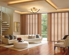 Create an inspired sense of refinement without sacrificing comfort with Hunter Douglas  Skyline® Gliding Window Panels. A perfect window treatment solution for a large expanse of windows. ♦ Hunter Douglas window treatments #LivingRoom #SpiralStaircase