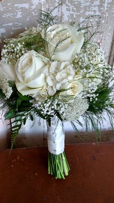 White bridal bouquet with hydrangea, roses, baby's breath and queen Anne's lace.