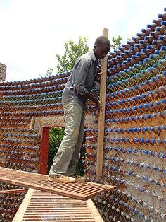A two-bedroom home with a bathroom, a kitchen, and a living room can be made from 14,000 plastic bottles and mud.