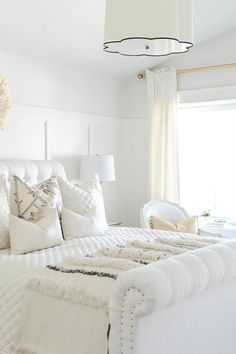 Elegant white bedroom with tufted headboard.