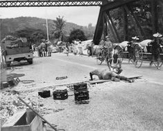 Royal Engineers prepare to blow up a bridge in Malaya during the British retreat to Singapore. In the background Chinese rickshaws loaded with rice from abandoned government stocks are crossing the bridge. The Allied forces under General Arthur Percival surrendered to General Yamashita in Singapore on 15 February 1942 after a Japanese campaign in Malaya lasting nearly 70 days.