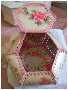 In the pink! Designed with floral postcards, this vintage hexagonal keepsake box has so much Cottage charm~    The pink crochet work is adorable and the vintage postcards are covered in a clear vinyl. The box is higher one side, from years of storage. A simple fix is to fill it with soaps, photographs, shells or keepsakes to help keep its shape~    Measures 7 1/2 wide x 3 1/2 high