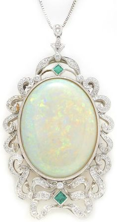 An opal, diamond and emerald pendant/brooch, Sophia D., with fourteen karat white gold chain. Oval-shaped opal cabochon measuring approximately: 32.8 x 24.6 x 10.0mm; signed Sophia D., no. 2167; mounted in platinum; pendant/brooch length: 2 11/16in.; chain length: 24in. Via Bonhams.