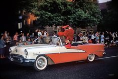 """Circus parade, 1958."" Mr. Bear in a 1955 Oldsmobile Starfire, probably in Baltimore."
